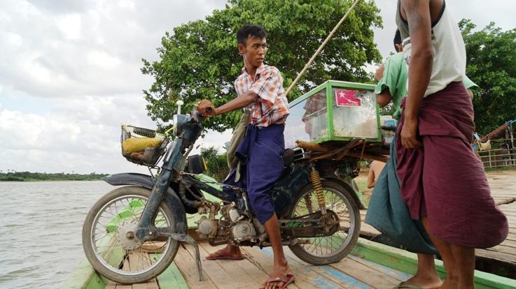 Loading motorcycle on a boat Myanmar